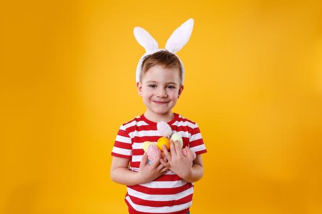 Portret van een aanbiddelijk glimlachend jongetje dat konijntjesoren draagt