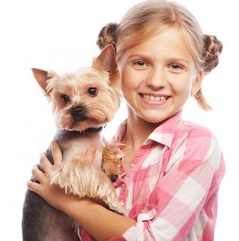 Portret van een aanbiddelijk jong meisje dat houdend een leuk puppy glimlacht