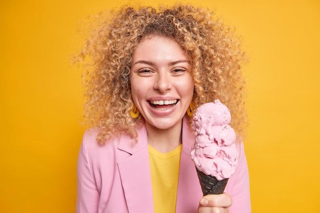 Portret van een aangenaam ogende vrouw met krullend haar houdt kegelijs vast en heeft vrije dag wandelingen met vrienden in het park in de zomer geïsoleerd over gele muur. vrouwelijk model eet lekker dessert