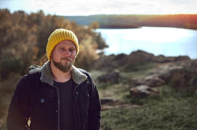 Portret van een aangenaam reizigermannetje met gele wollen hoed met een rugzak op een landschap
