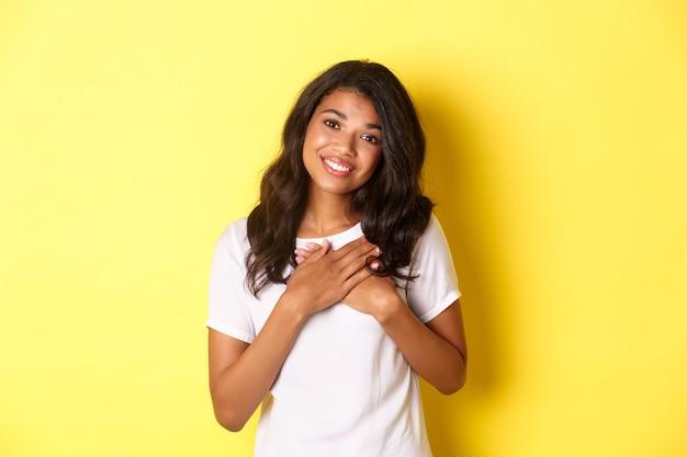 Portret van een aangeraakt en tevreden afro-amerikaans meisje, hand in hand op het hart, bedankt en glimlachen, verrukt over gele achtergrond.