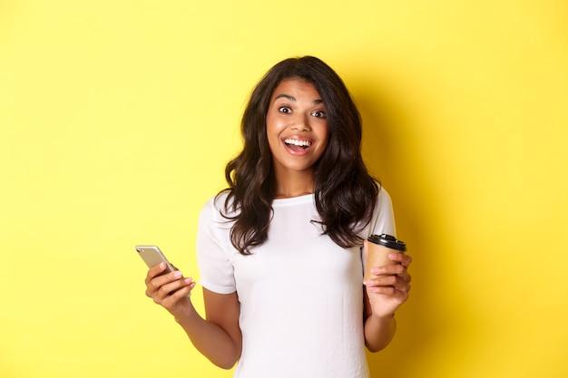 Portret van een aantrekkelijk afrikaans-amerikaans meisje dat lacht, koffiekopje en smartphone vasthoudt en over een gele achtergrond staat
