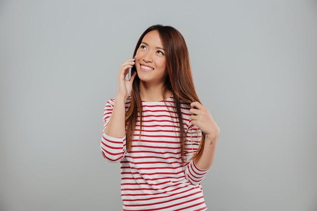 Portret van een aantrekkelijk aziatisch meisje dat op mobiele telefoon spreekt