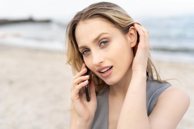 Portret van een aantrekkelijk blond meisje dat op de mobiele telefoon op het strand praat met een verbluffende look