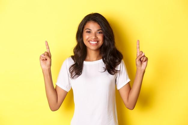 Portret van een aantrekkelijk en zelfverzekerd afrikaans-amerikaans vrouwelijk model met een wit t-shirt dat wijst