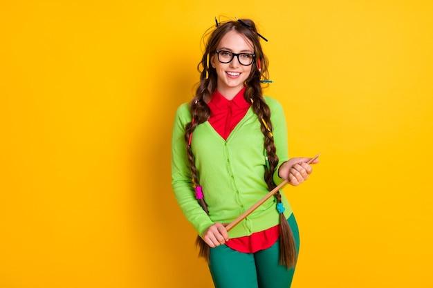 Portret van een aantrekkelijk funky vrolijk intellectueel meisje dat in de hand de aanwijzerwetenschap vasthoudt, geïsoleerd over een levendige gele kleurachtergrond