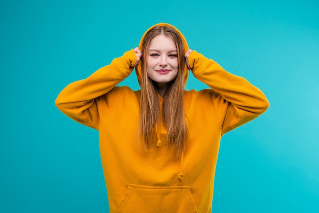 Portret van een aantrekkelijk hipstermeisje in een gele die hoodie over blauwe achtergrond wordt geïsoleerd