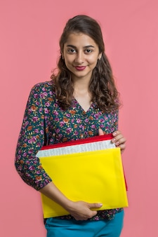 Portret van een aantrekkelijk indisch meisje, vrouwelijke student die een omslag en een boek houdt.