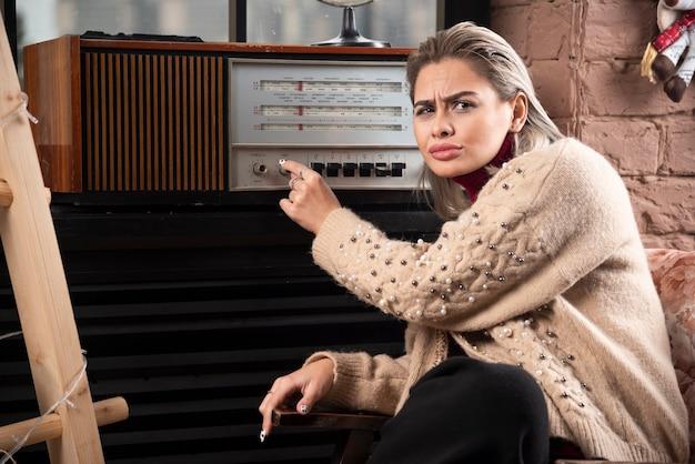 Portret van een aantrekkelijk jong meisje dat platenspeler draait terwijl zittend en wegkijkend