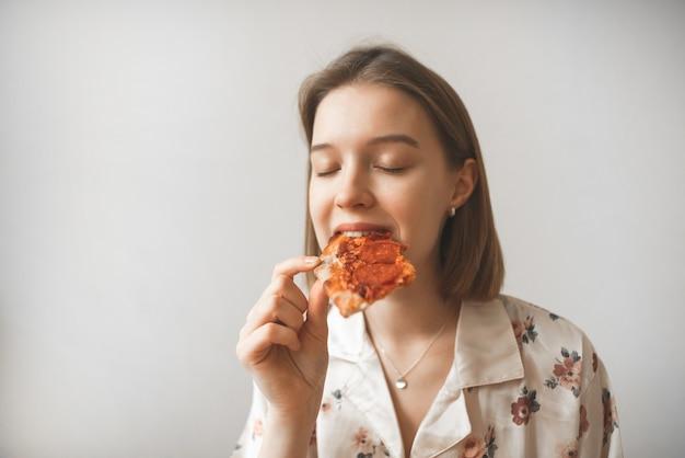 Portret van een aantrekkelijk meisje eet een stuk pizza met haar ogen dicht