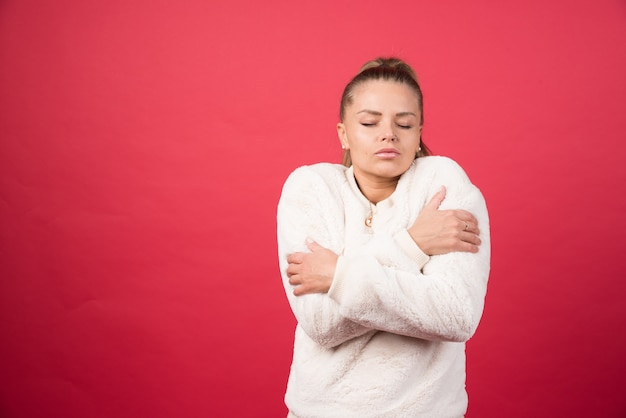 Portret van een aantrekkelijk meisje knuffelen zichzelf geïsoleerd op rode achtergrond