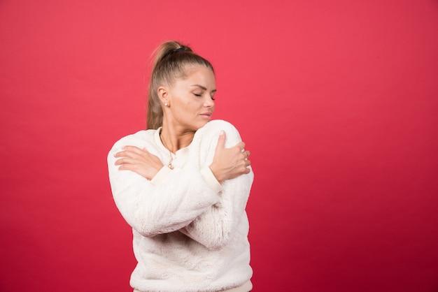 Portret van een aantrekkelijk meisje knuffelen zichzelf geïsoleerd over rode muur