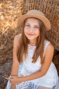 Portret van een aantrekkelijk meisje met een baal stro op de achtergrond