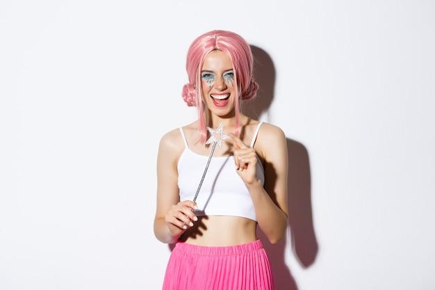 Portret van een aantrekkelijk meisje met een roze pruik en lichte make-up, verkleed als een fee voor een halloweenfeest, met een toverstaf en een glimlach