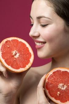 Portret van een aantrekkelijk meisje met een schijfje grapefruit op een rode achtergrond