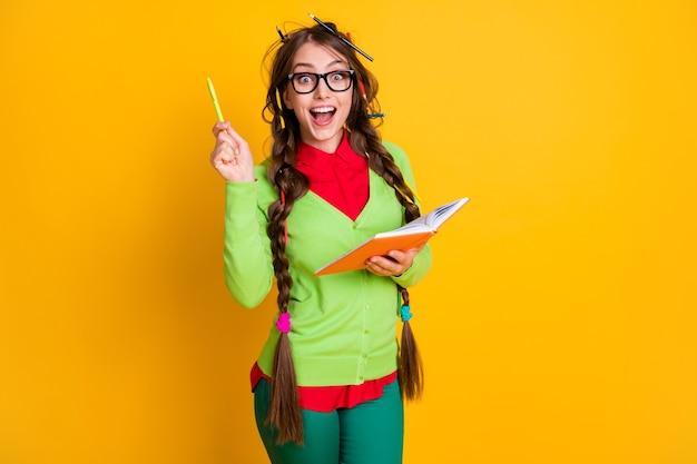 Portret van een aantrekkelijk opgewonden, intelligent genie, vrolijk tienermeisje dat een essay-oplossing schrijft die over een felgele kleurachtergrond wordt geïsoleerd