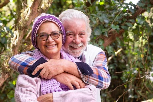 Portret van een aantrekkelijk stel senior man en vrouw die genieten van een bergexcursie in het bos in het herfstseizoen, omarmen en glimlachen terwijl ze naar de camera kijken - actieve gepensioneerde ouderen en leuk concept