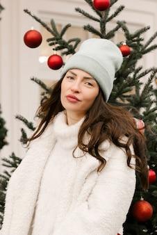 Portret van een aantrekkelijk stijlvol meisje in een hoed met een kerstboom