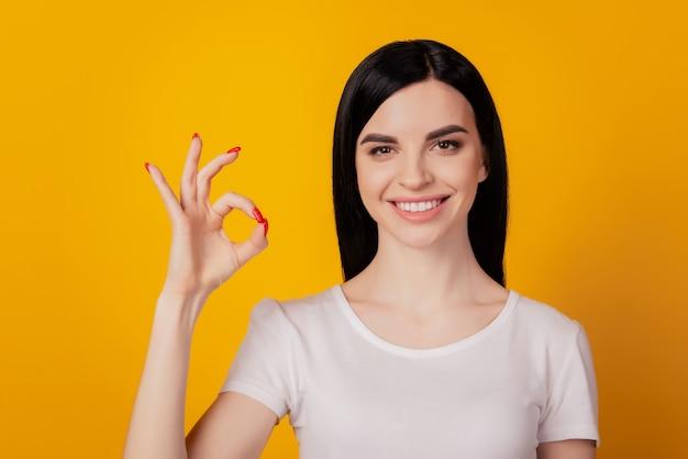 Portret van een aantrekkelijk vrolijk meisje dat een ok-teken-advertentieoplossing toont die over een felgele kleurachtergrond wordt geïsoleerd