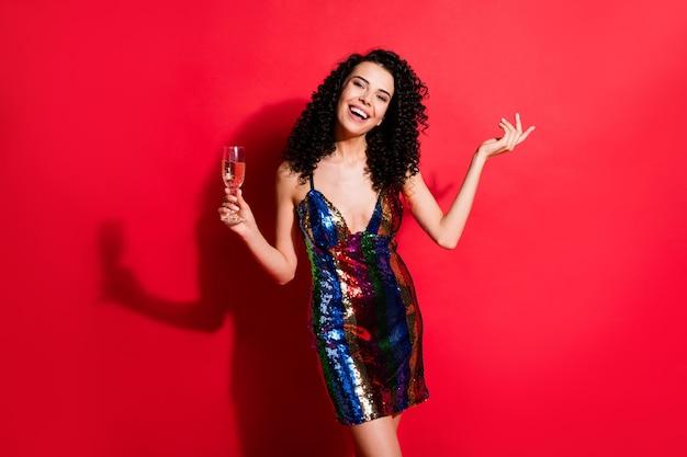 Portret van een aantrekkelijk vrolijk meisje met golvend haar dat wijn drinkt, ontspan je geïsoleerd op een heldere, levendige, levendige rode kleurachtergrond