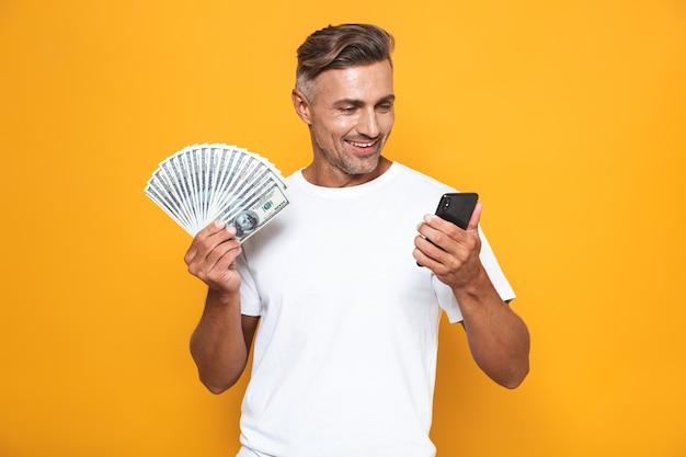 Portret van een aantrekkelijke 30-jarige man in een wit t-shirt met een mobiele telefoon en een hoop geld geïsoleerd op geel