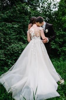Portret van een aantrekkelijke achterbruid die de bruidegom omhelst en kust. huwelijksceremonie. pasgetrouwden trouwen in het bos.