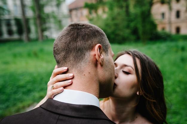 Portret van een aantrekkelijke achterbruid die de bruidegom omhelst en kust.