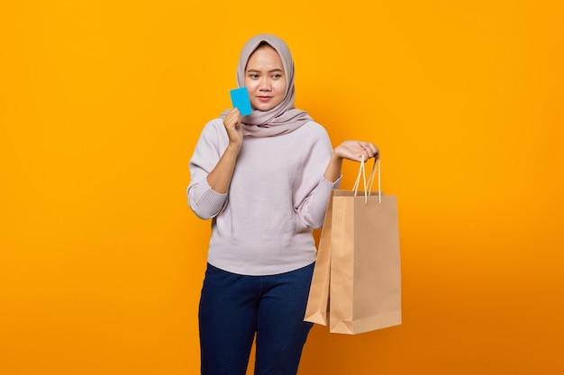 Portret van een aantrekkelijke aziatische vrouw die een boodschappentas vasthoudt en een creditcard toont op een gele achtergrond
