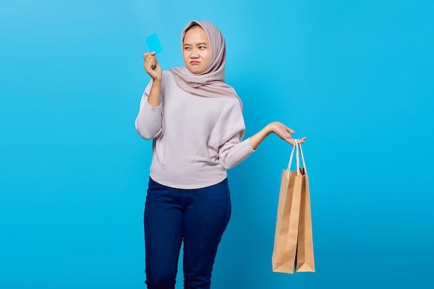 Portret van een aantrekkelijke aziatische vrouw die een boodschappentas vasthoudt en een creditcard toont over een blauwe achtergrond