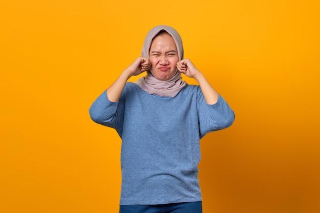 Portret van een aantrekkelijke aziatische vrouw die gestrest en bezorgd over een gele achtergrond kijkt