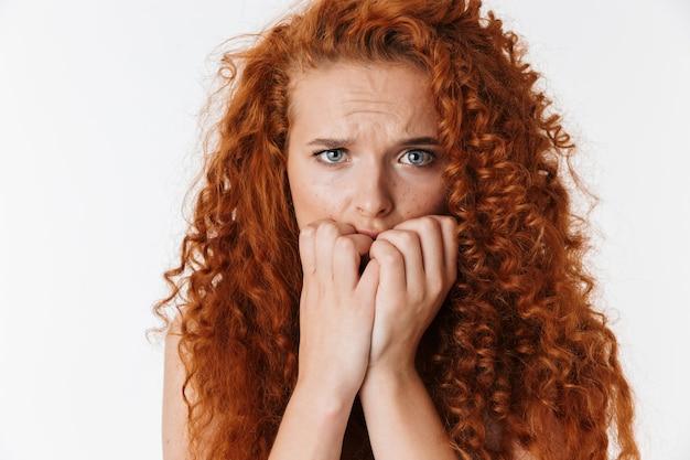 Portret van een aantrekkelijke, bange jonge vrouw met lang krullend rood haar dat geïsoleerd staat