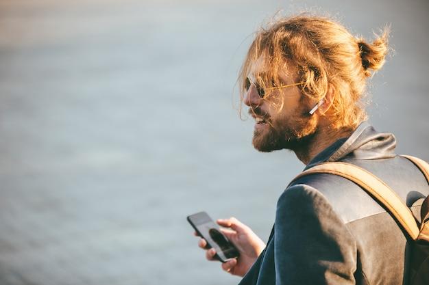 Portret van een aantrekkelijke bebaarde man in oortelefoons
