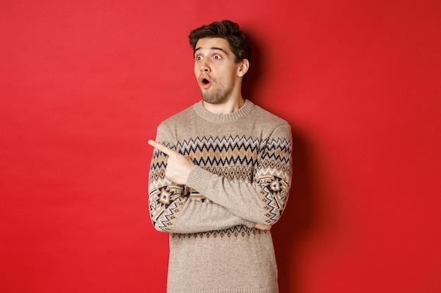 Portret van een aantrekkelijke blanke man die nieuwjaar, wintervakantie viert, met de vinger wijst en verrast naar links kijkt, kerstadvertentie toont, over rode achtergrond staat.