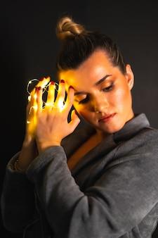 Portret van een aantrekkelijke blanke vrouw met lichtslingers om haar handen gewikkeld