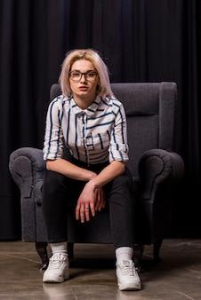 Portret van een aantrekkelijke blonde jonge vrouw zittend op fauteuil camera kijken