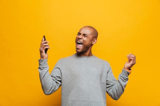 Portret van een aantrekkelijke, boze, casual jonge afrikaanse man die over een gele muur staat en een mobiele telefoon vasthoudt