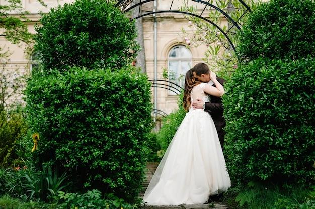 Portret van een aantrekkelijke bruid die de bruidegom omhelst en kust.