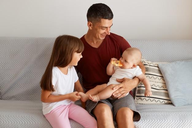 Portret van een aantrekkelijke brunette man met een kastanjebruin t-shirt die tijd doorbrengt met zijn kinderen, familie zittend op de bank, positieve emoties uiten, samen genietend van het weekend.