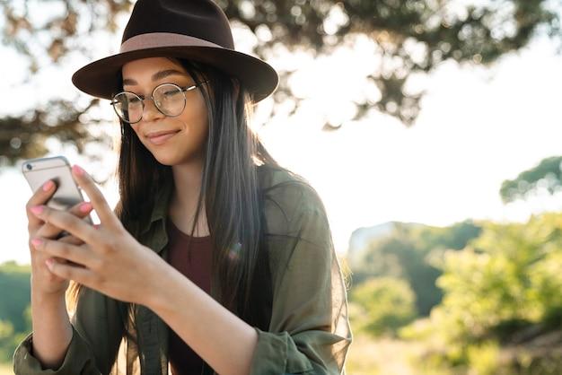 Portret van een aantrekkelijke brunette vrouw met een stijlvolle hoed en bril die een mobiele telefoon gebruikt terwijl ze op zonnige dag in een groen park wandelt