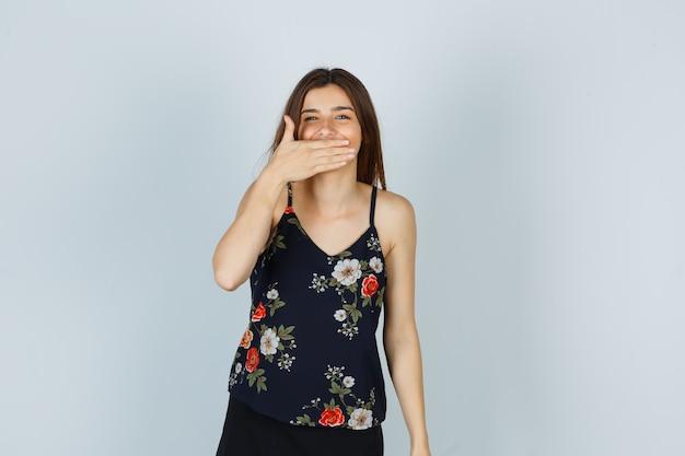 Portret van een aantrekkelijke dame die de mond bedekt met de hand in de blouse en er vrolijk vooraanzicht uitziet