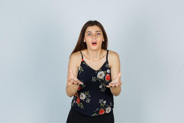 Portret van een aantrekkelijke dame die een vraaggebaar maakt in een blouse en een geschokt vooraanzicht kijkt