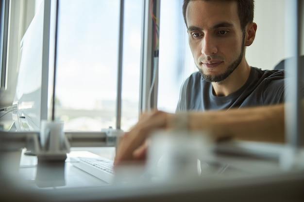 Portret van een aantrekkelijke geconcentreerde bebaarde serieuze jonge mannelijke ingenieur die in een onderzoekslaboratorium werkt
