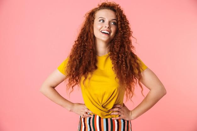 Portret van een aantrekkelijke gelukkige jonge vrouw met lang krullend rood haar geïsoleerd, handen op de heupen