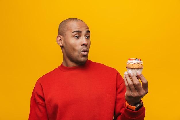 Portret van een aantrekkelijke geschokte casual jonge afrikaanse man die over een gele muur staat en naar cupcake kijkt