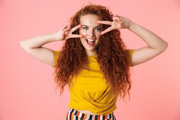 Portret van een aantrekkelijke glimlachende jonge vrouw met lang krullend rood haar dat geïsoleerd staat, vredesgebaar