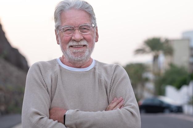 Portret van een aantrekkelijke glimlachende senior man met een bril die in een verlaten straat staat en naar de camera kijkt.