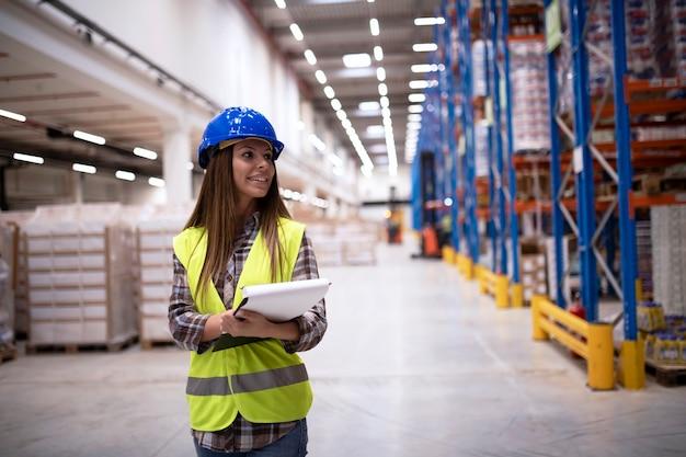 Portret van een aantrekkelijke glimlachende supervisor die van de magazijnmedewerker door de grote afdeling van de fabrieksopslag loopt die naar planken kijkt