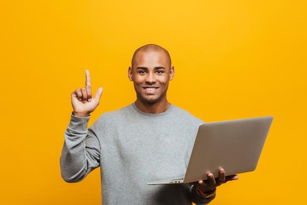 Portret van een aantrekkelijke glimlachende, zelfverzekerde, casual jonge afrikaanse man die over de gele muur staat, een laptop vasthoudt en de vinger omhoog wijst