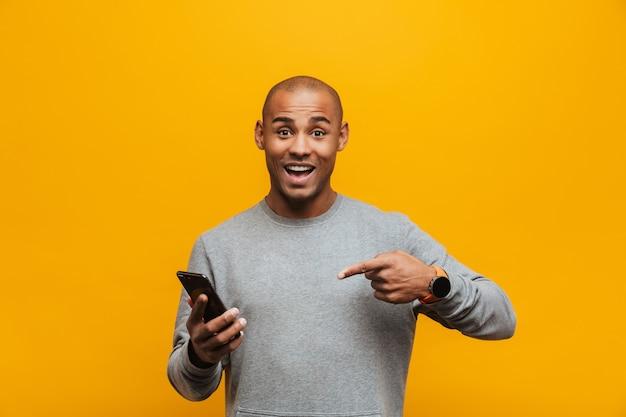 Portret van een aantrekkelijke glimlachende, zelfverzekerde, casual jonge afrikaanse man die over de gele muur staat en met de vinger naar de mobiele telefoon wijst