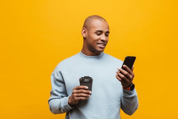 Portret van een aantrekkelijke glimlachende, zelfverzekerde, casual jonge afrikaanse man die over de gele muur staat, met behulp van mobiele telefoon